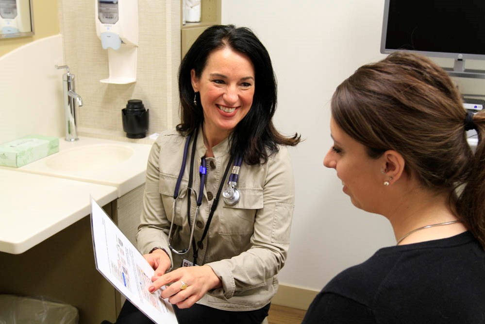 Image of a physician speaking with a patient in an exam room