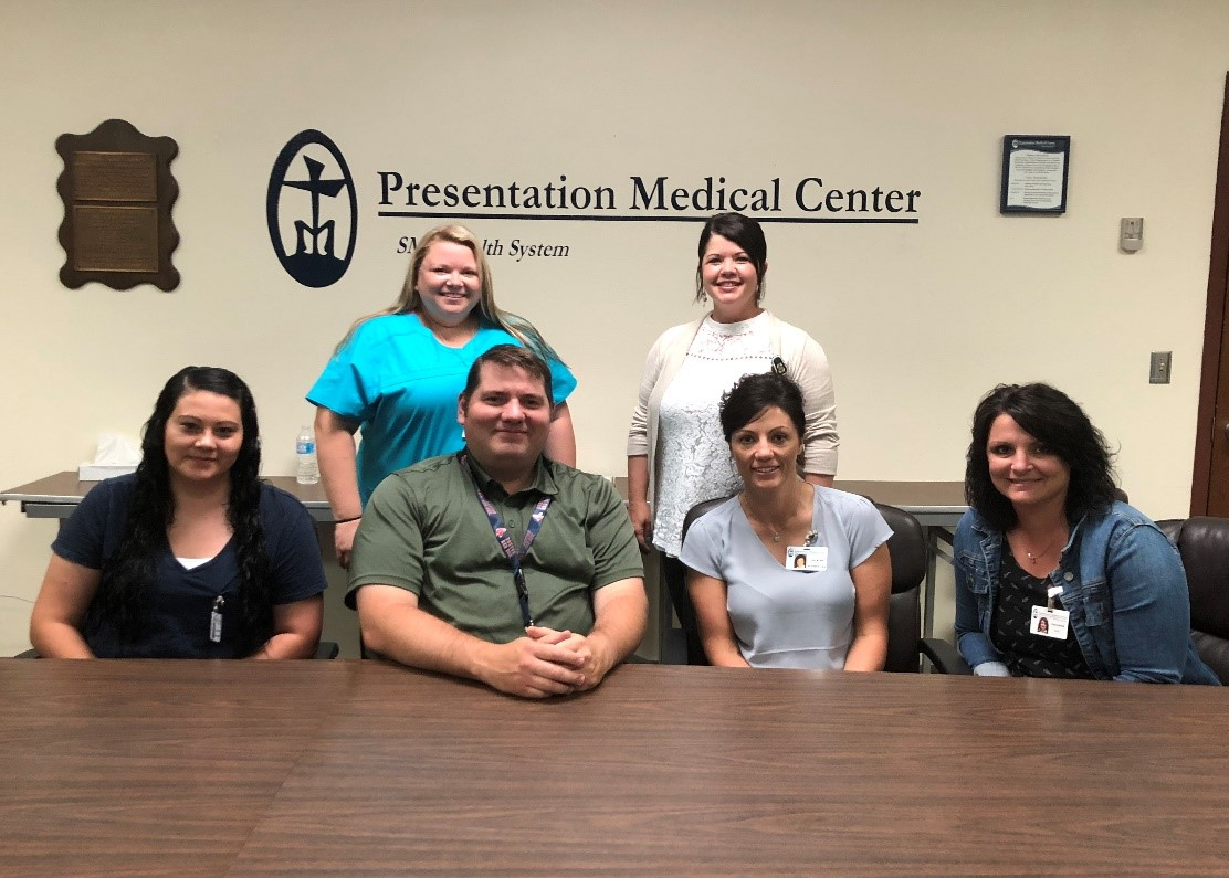 Pictured front row: Mandy Swain, Administrative Assistant, Chris Albertson, CEO, Lori Martinson, VP of Patient Services, Paula Wilkie, CFO; back row: Sarah Gailfus, Clinic Coordinator, Nikki Wilkes, Director of Care Coordination; not pictured: Wade Burges