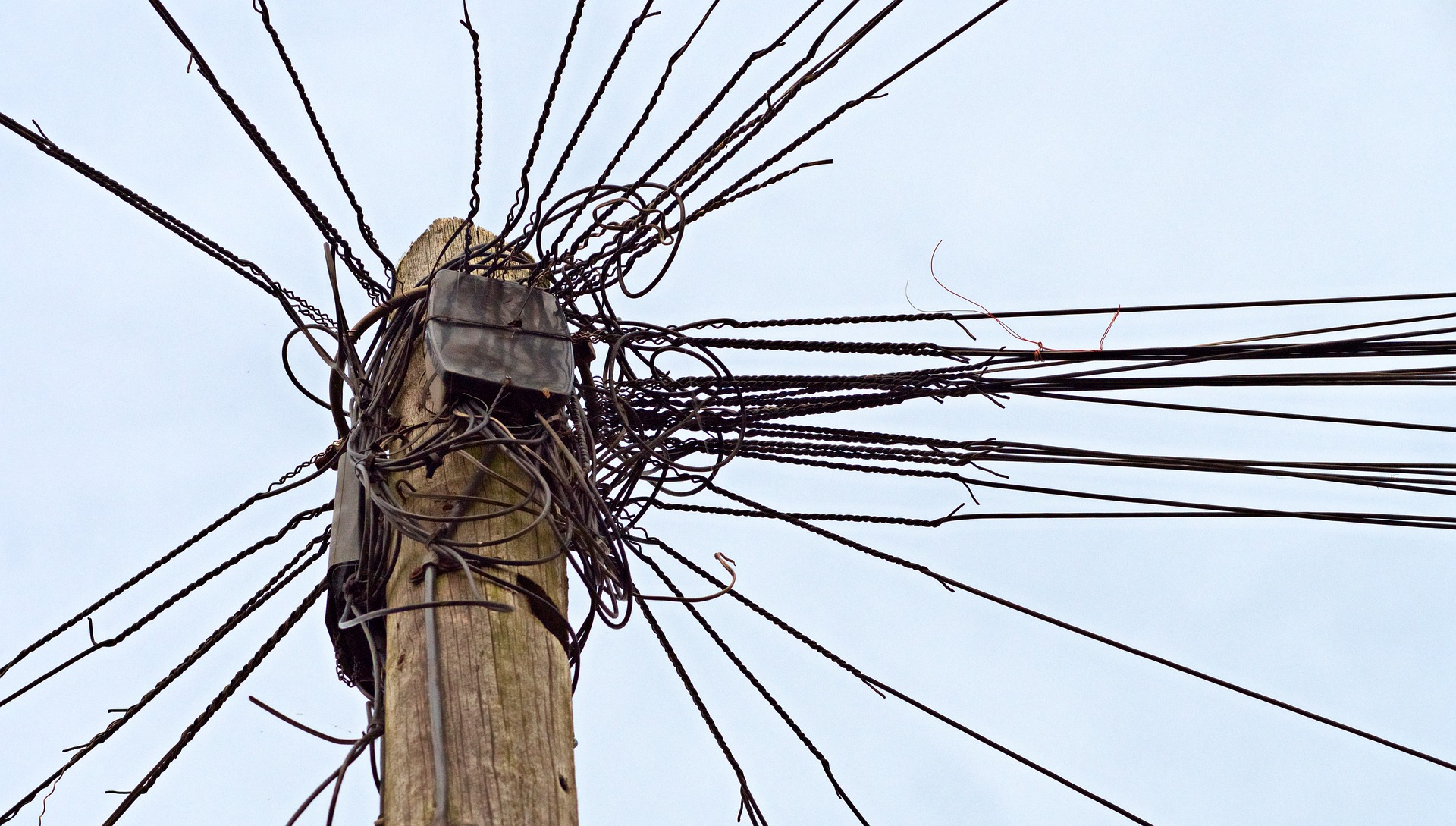 Image of a telephone pole with many different lines connected to it