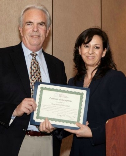 Hospital CEO Bob Schapper receiving award from Angelica Perez, State Flex Coordinator, California